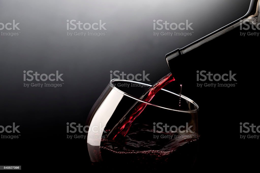 Red wine pouring into wine glass stock photo