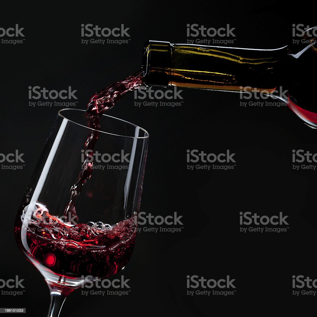 red wine pouring into wineglass isolated on black royalty-free stock photo