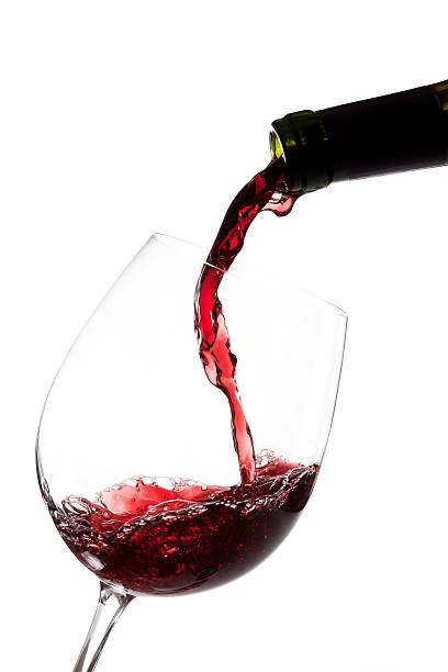 Red wine pouring on white background Red wine pouring into a wine glass pouring stock pictures, royalty-free photos & images