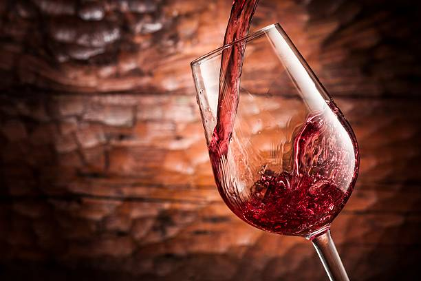 red wine pouring stock photo