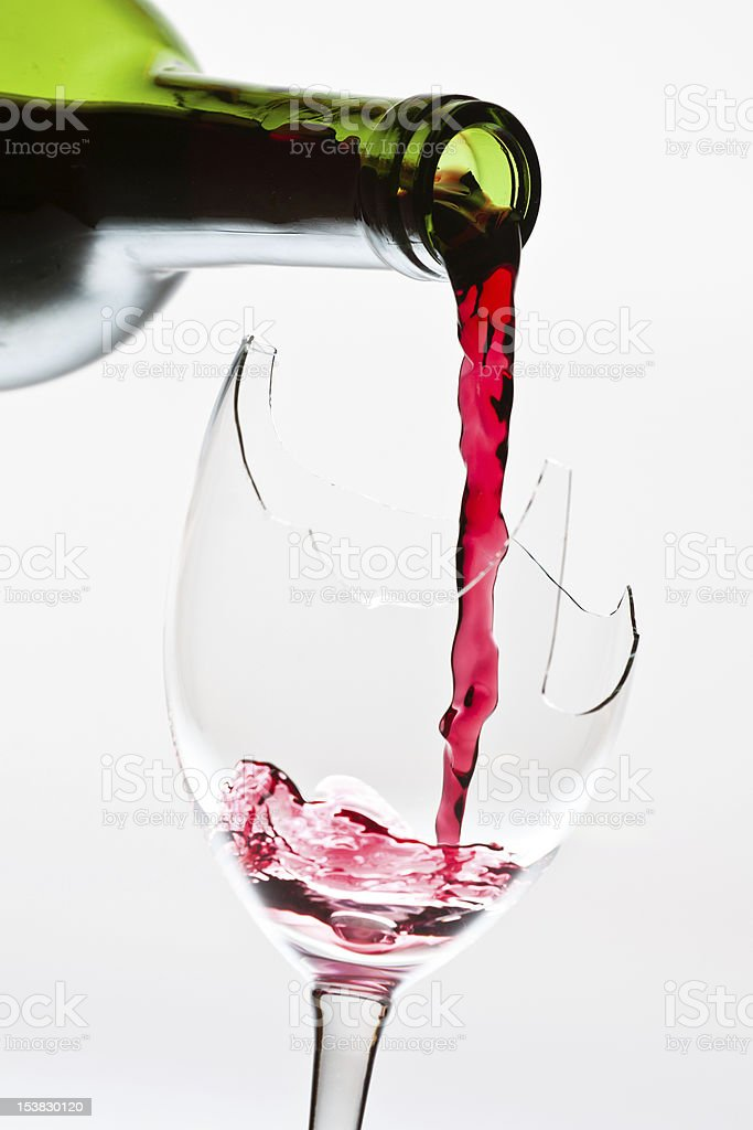 Red wine pouring to the broken glass stock photo