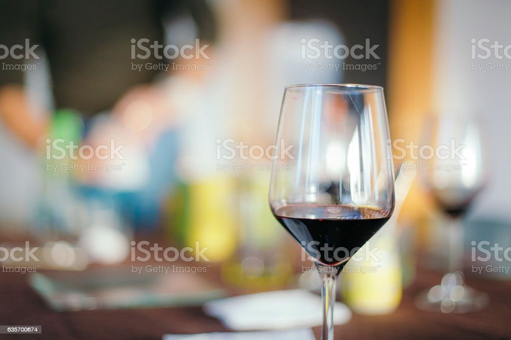 Red wine served on a wineglass on a blurred background royalty-free stock photo