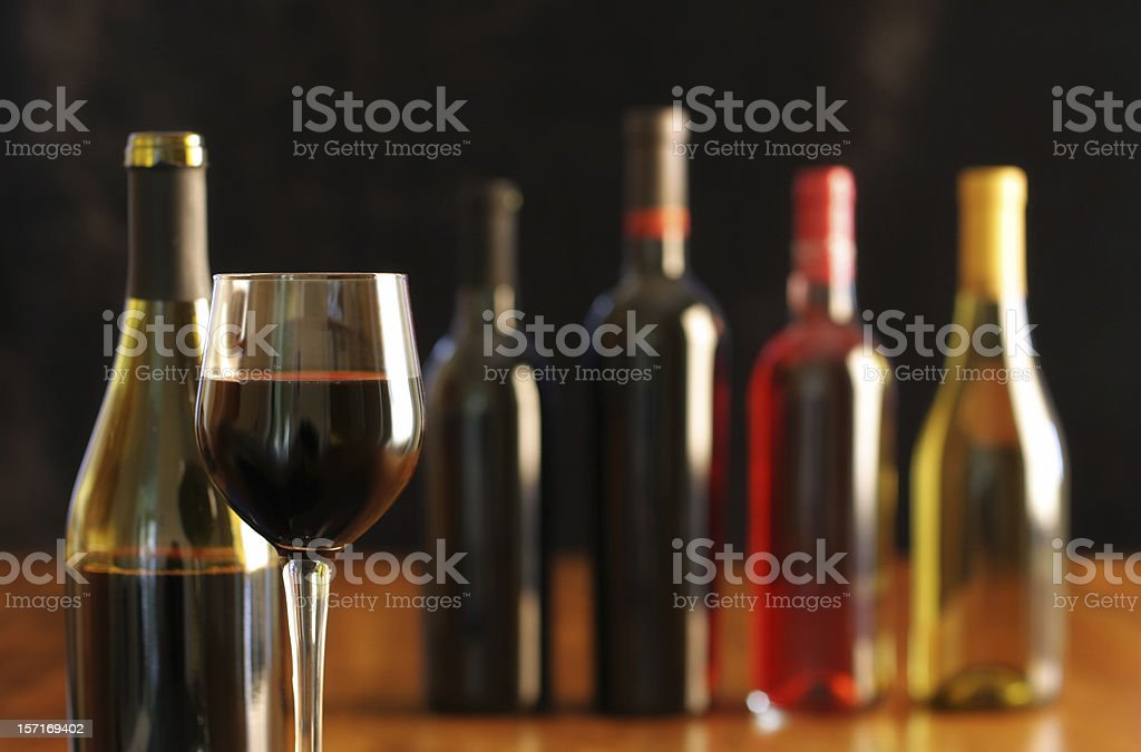 Red wine tasting with glass and various wine bottles royalty-free stock photo