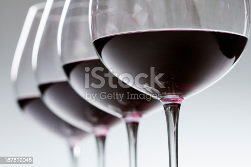 Red wine poured in four winetasting wineglasses in a row, for tasting and comparing fermented grape varieties served in each glass. The alcoholic beverage is a connoisseur favorite in the food and drink industry. Selective focus still life, diagonal close-up of small to medium group of objects, with no people.