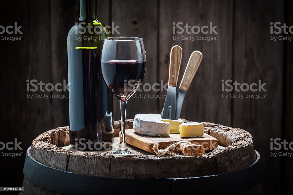 Red wine with camembert cheese on old barrel stock photo
