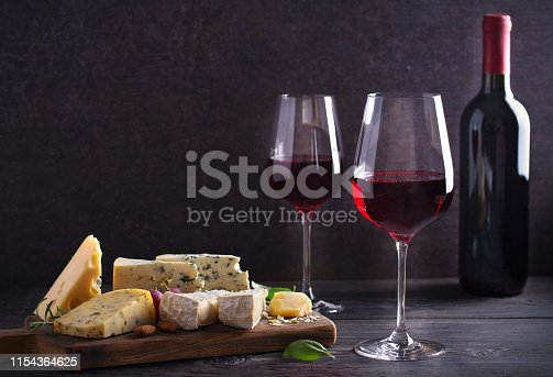 Red wine with cheese on chopping board. Wine and food concept - Image