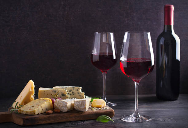 red wine with cheese on chopping board. wine and food concept - formaggio foto e immagini stock