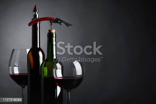 Glasses and bottles of red wine with corkscrew on a black background. Copy space for your text.