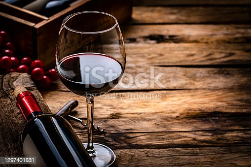istock Red wineglass and bottle. Copy space 1297401631