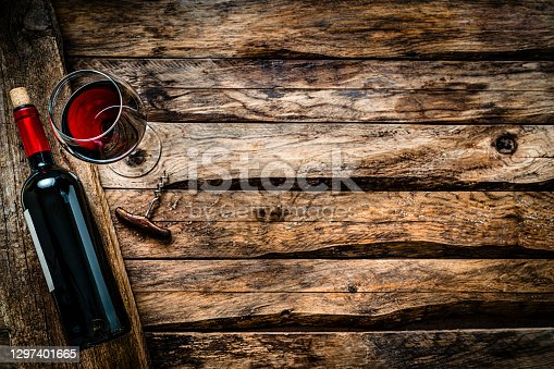 Overhead view of a red wineglass and a wine bottle shot on rustic wooden table. The composition is at the left of an horizontal frame leaving useful copy space for text and/or logo at the right. Predominant colors are brown and red. High resolution 42Mp studio digital capture taken with SONY A7rII and Zeiss Batis 40mm F2.0 CF lens