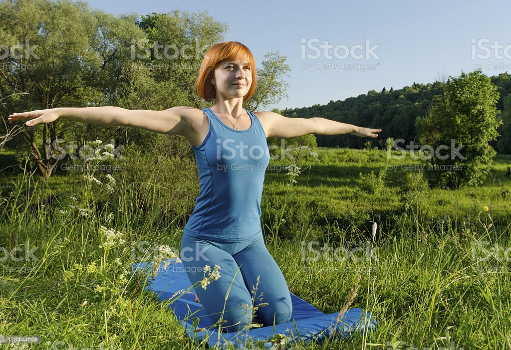 Red woman practicing fitness yoga outdoors stock photo