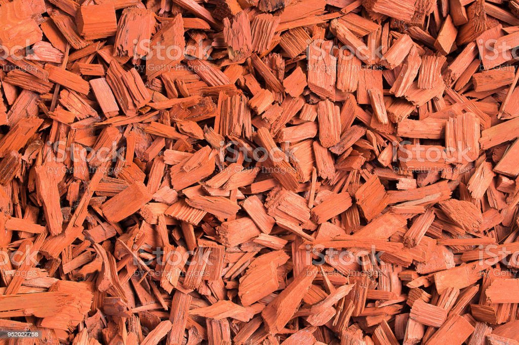 Red wood chips. Natural texture background of red wooden pieces of tree bark. Wood chips, mulch for gardening or natural themes. Full filled frame picture. Landscaping red colored materials. Above view. stock photo