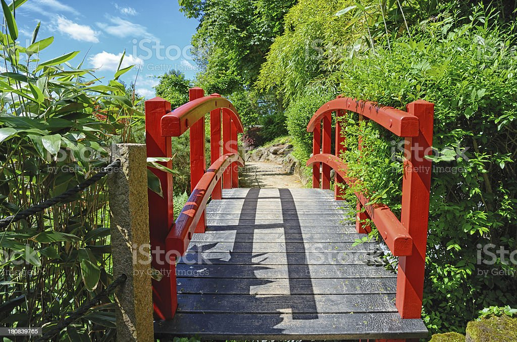 Red wood footbridge in japanese garden royalty-free stock photo