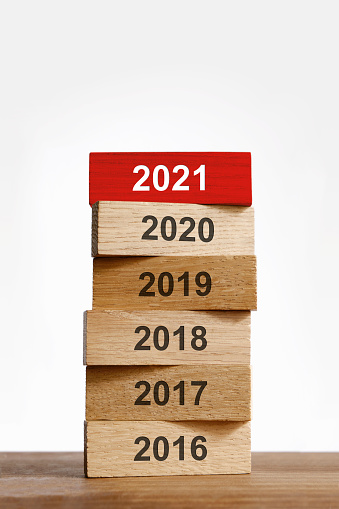 """Red wooden """"2021"""" block on top of other years, starting from 2016 to 2021"""