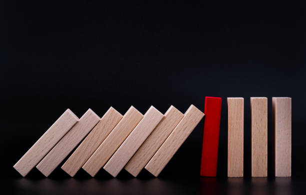 Red wooden block stopping the domino wooden effect. Alternative risk concept, business plan and business strategy. Insurance concept. stock photo