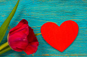istock red wooden heart shape and wine color tulip on turquoise rustic planks 1210967357