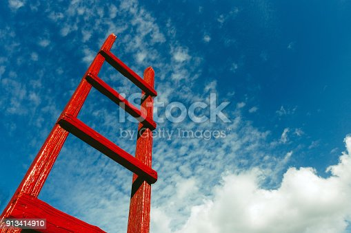 istock Red wooden staircase against the blue sky. Development Motivation Busines Career Heaven Growth Concept 913414910