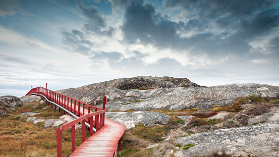 Red wooden walkway along the natural rocky Ilulissat Icefjord Coast under dramatic twilight skyscape, Panorama view along the greenlandic artic coast covered with green mosses. Ilulissat Icefjord Coast, Ilulissat, Greenland, Denmark, Arctic Polar Region