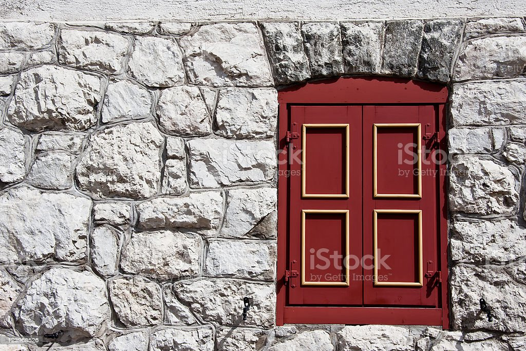 Red Wooden Window on White Wall of Rocks royalty-free stock photo