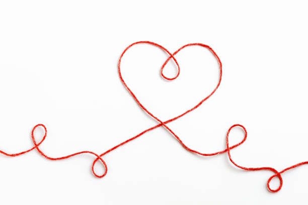 Red woolen thread in the shape of heart on white background stock photo