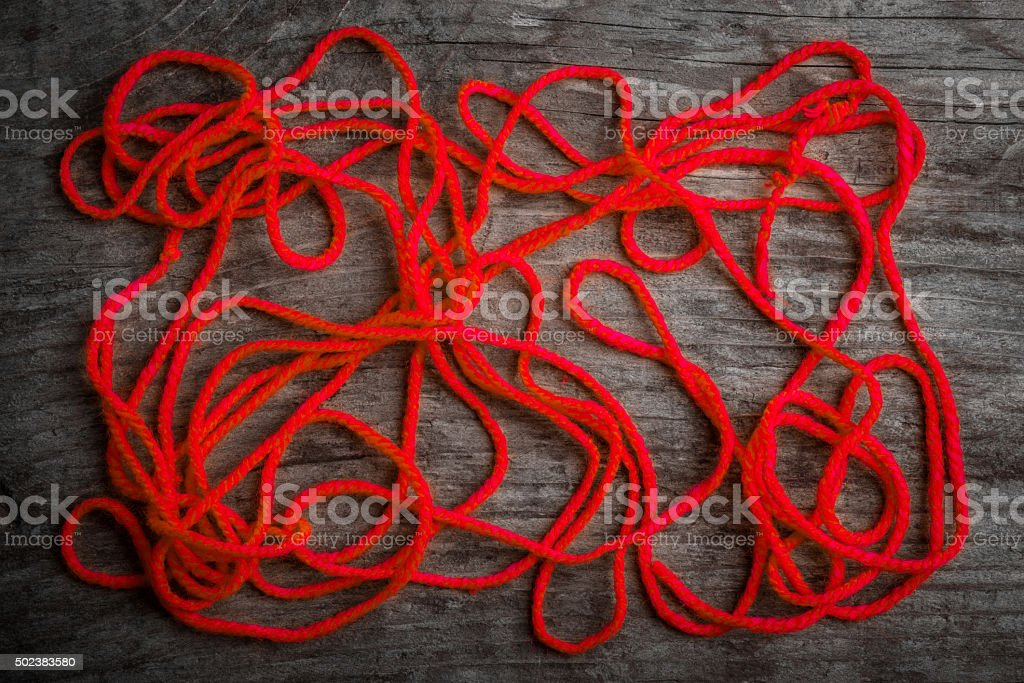 red woolen thread on wood background stock photo