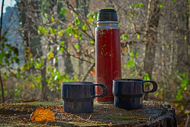 red worn out thermos bottle with two blue cups - heißes wasser trinken stock-fotos und bilder