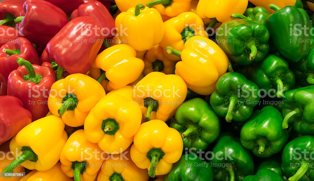 Red, yellow, and green bell peppers (capsicum) background stock photo