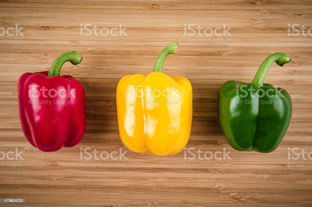 Red, yellow and green bell peppers on wooden table stock photo
