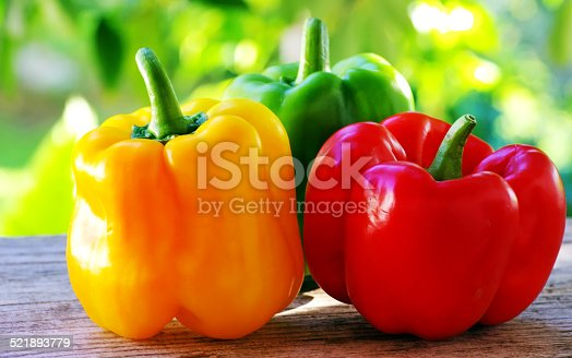 red, yellow and green pepper on table,green background
