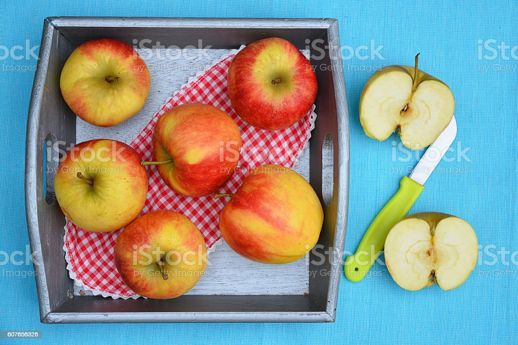 Red, yellow cut apples in wooden basket with green knife stock photo