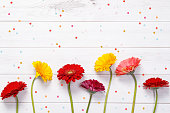 Red, yellow gerbera flowers with confetti on wooden background. Holiday, Easter, Birthday concept.