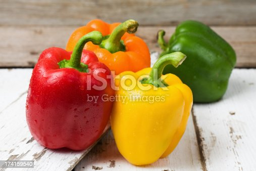 Whole red, yellow, orange and green bell peppers on old painted and peeling wood boards.