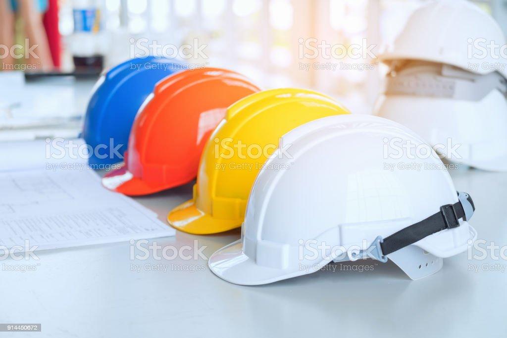 Rot-gelb-weiß und blau Sicherheit Schutzhelm auf den Bauplan mit Vertrag Ordner als Hintergrund. Ingenieur-Work-Schreibtisch-Konzept. Die Fraktion der Helm und die Blaupause auf Baustelle – Foto
