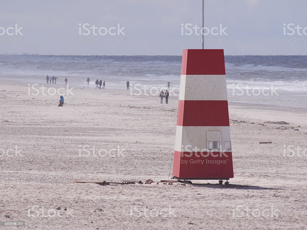 Red-and-white tower at the beach stock photo