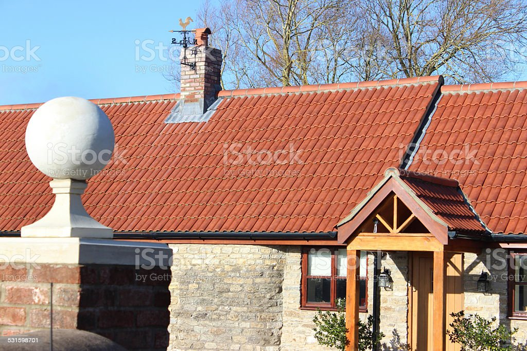 Red-brick gate-post, stone ball finial / pier-cap, barn-conversion bungalow, open porch stock photo