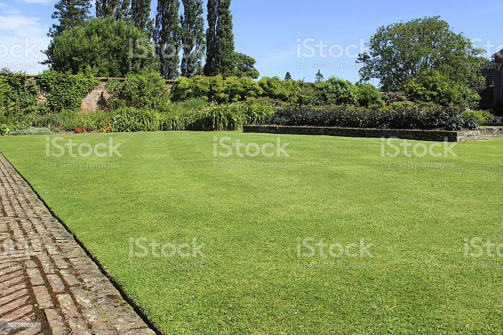 Red-brick path, block-paving, paved pathway image, herbaceous-border, flowers, lawn, lombardy-poplars stock photo