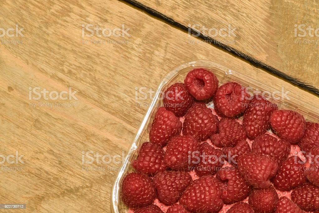 Red-fruited raspberries in plastic box on wooden background. Raspberries background. Close-up stock photo