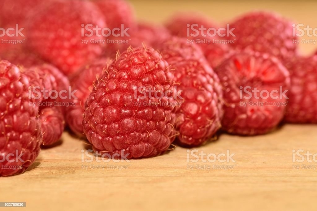 Red-fruited raspberries on wooden background. Raspberries background. Close-up stock photo