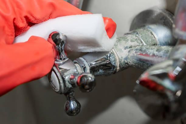 Une main à gants rouges frotte un bouton d'eau chaude sur un robinet chromé recouvert de calcaire avec une éponge à mélamine blanche. Orientation sélective. Vue de plan rapproché - Photo