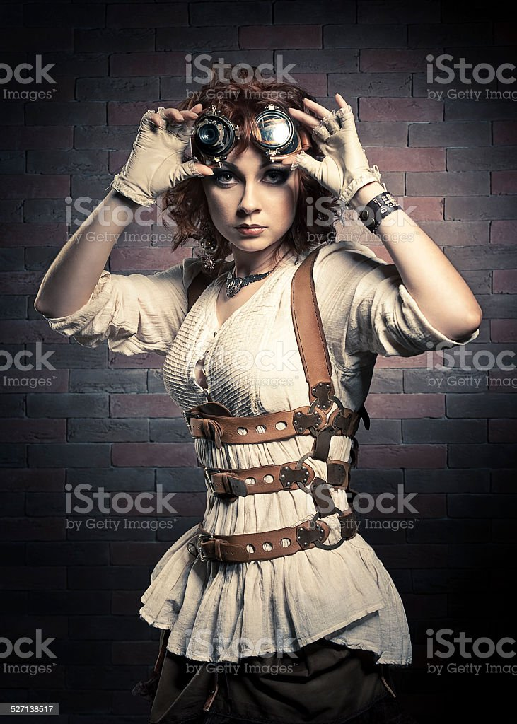 Redhair girl with steampunk goggles stock photo
