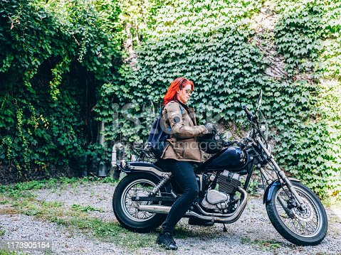 Red hair Caucasian woman with her vintage motorcycle.