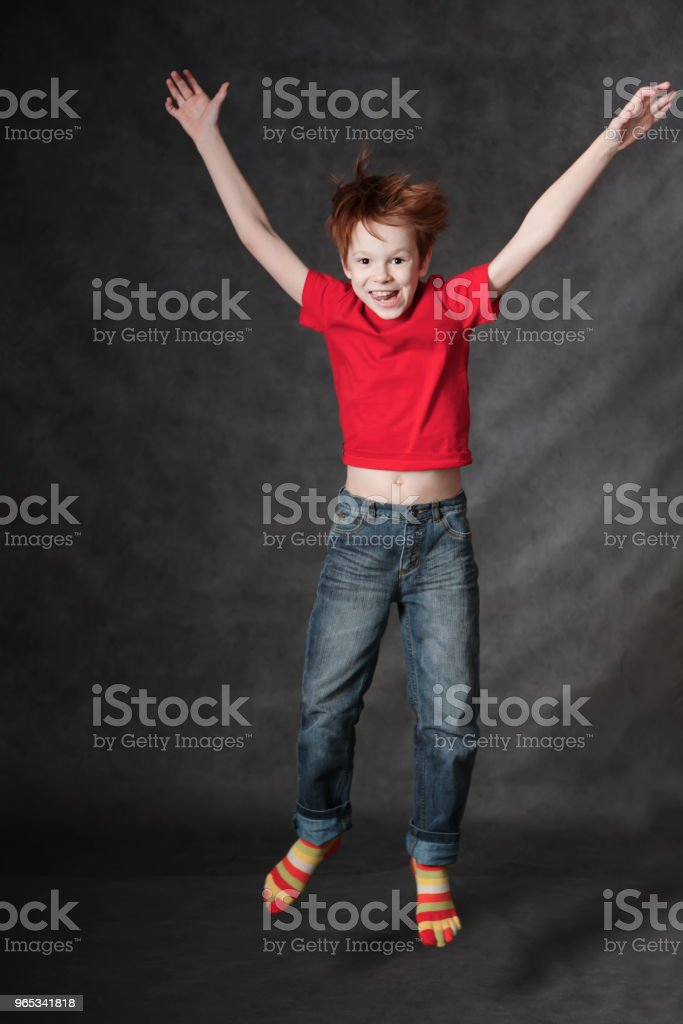 Red-haired boy jumping on a dark background. Studio photography zbiór zdjęć royalty-free