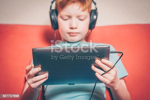 istock Red-haired boy sitting on the couch listening to an audiobook on a tablet 937707898