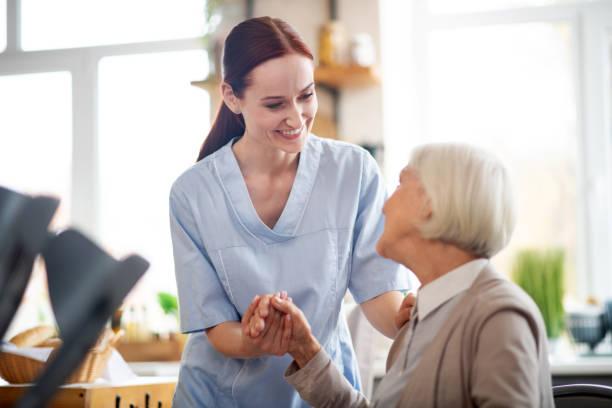 Rothaarige Betreuerin lächelnd und im Gespräch mit betagten Frau – Foto