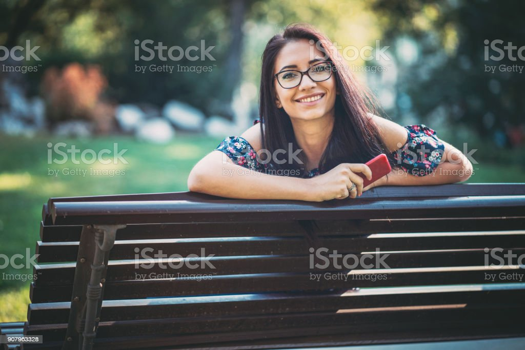 Red-haired female holding her mobile phone and looking at camera stock photo