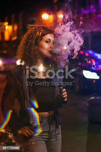 Young attractive red-haired girl smokes electronic cigarette. She walks down street. Evening city lights and signs flashing. Alternative to tobacco smoking