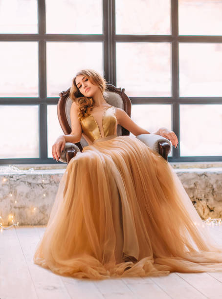rothaariges mädchen mit einer abend-frisur in einem luxuriösen, teure goldenen kleid - tüllkleid stock-fotos und bilder