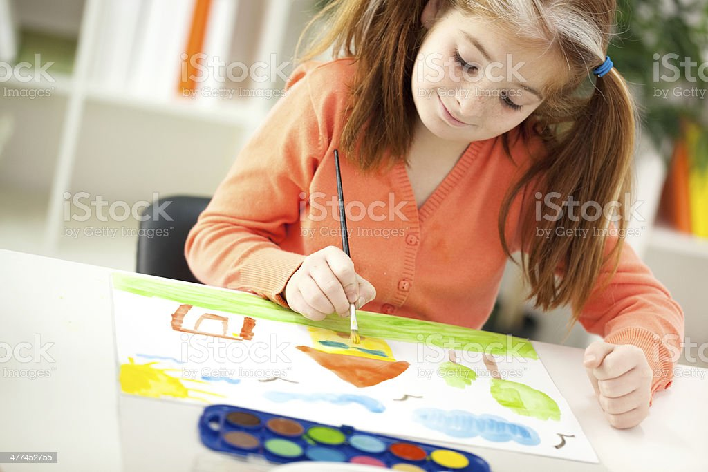 red-haired girl with pigtails drawing stock photo