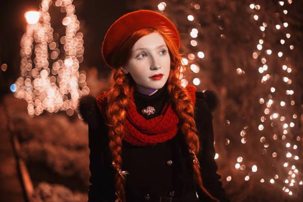 rothaariges mädchen mit roten lippen rote mütze und schal stehen vor dem hintergrund des weihnachtsbaumes. farbige bokeh. zusammenfassung hintergrund. goldener kranz. silvester nacht. kalten abend. kunst - schal mit sternen stock-fotos und bilder