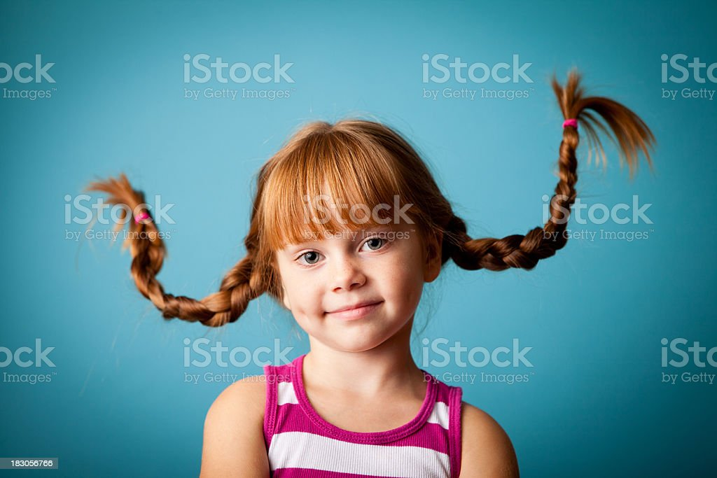 Red-Haired Girl with Upward Braids, a Smile and Dimples royalty-free stock photo